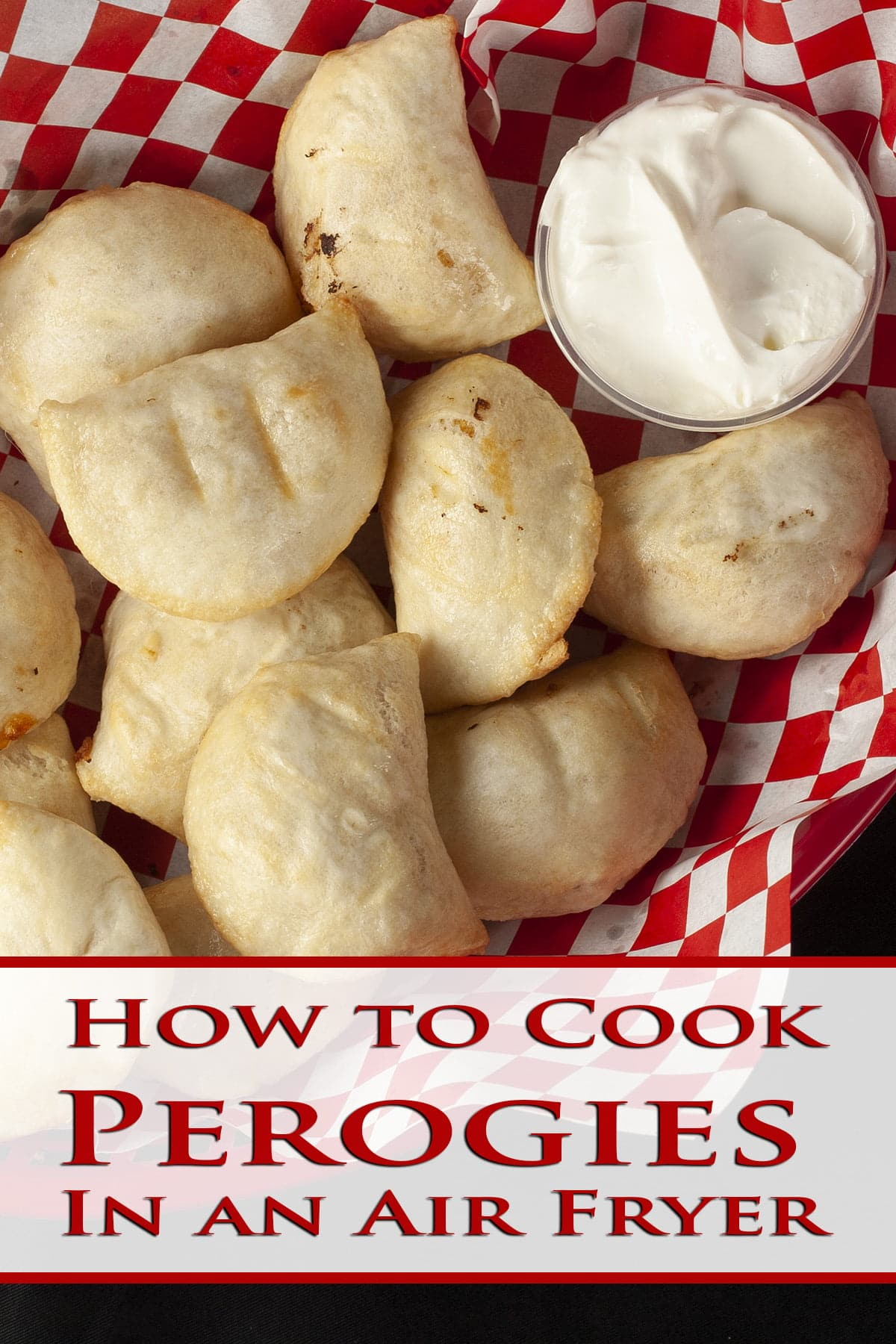 Perfectly air fried perogies are mounded in a red basket, accompanied by a small bowl of sour cream.