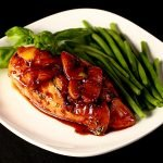 Plate with one chicken breast topped with sliced peaches and a reddish-brown sauce, with green beans on the side.