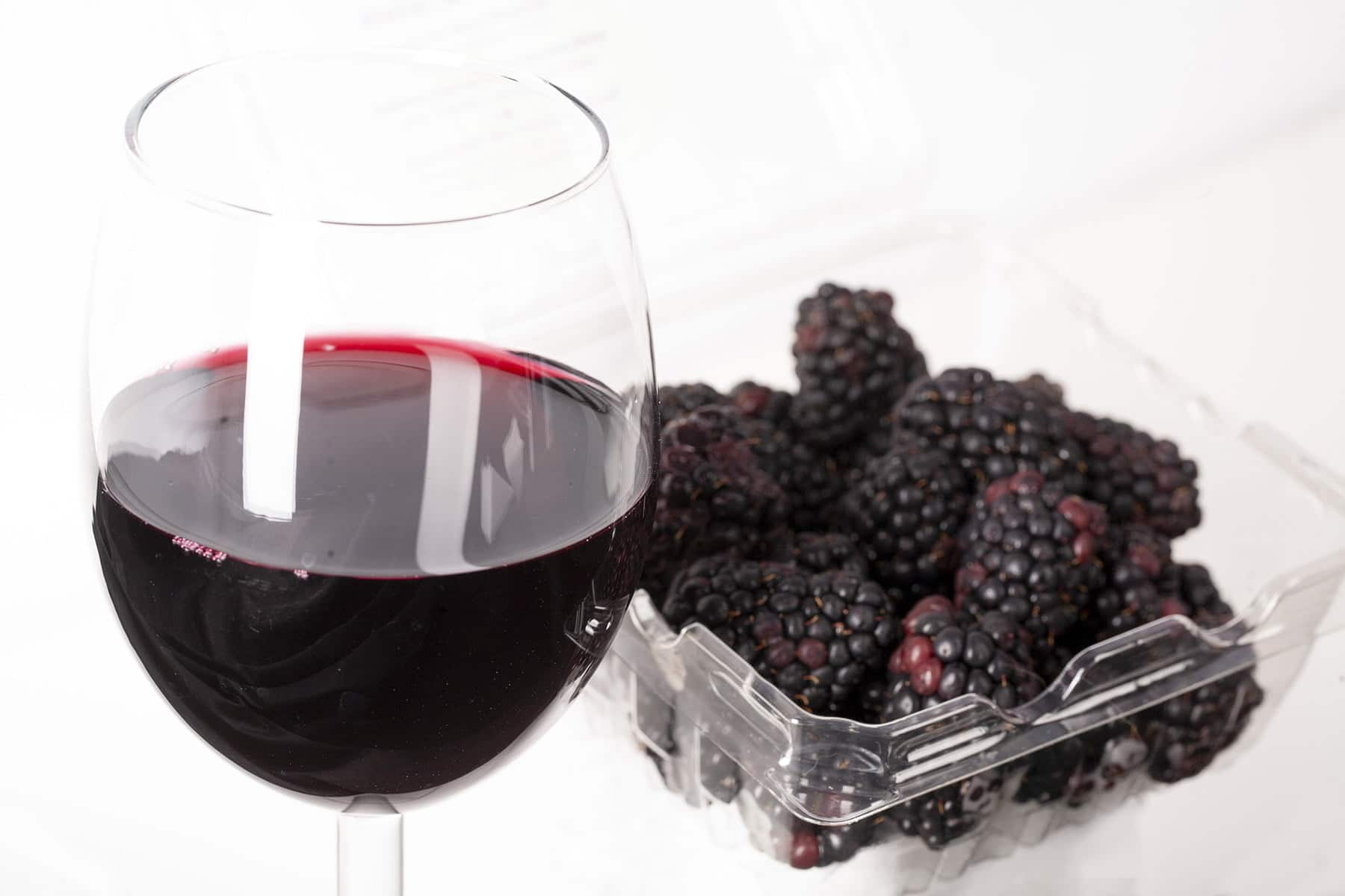 A glass of deep purple blackberry wine in front of a tray of blackberries.
