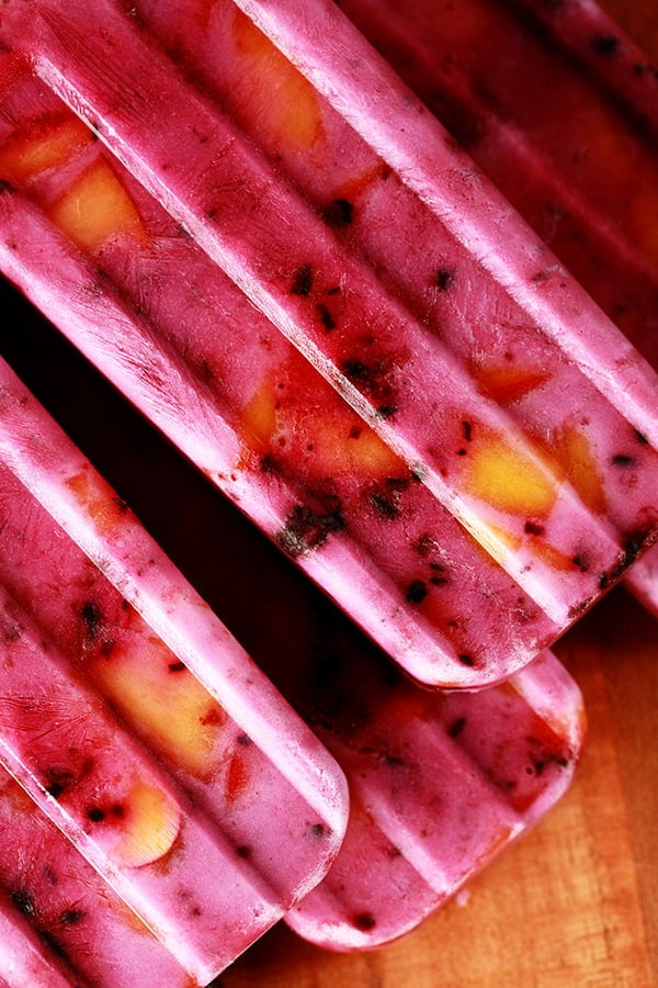 Close up image of light purple popsicles with chunks of blackberries and peaches in them