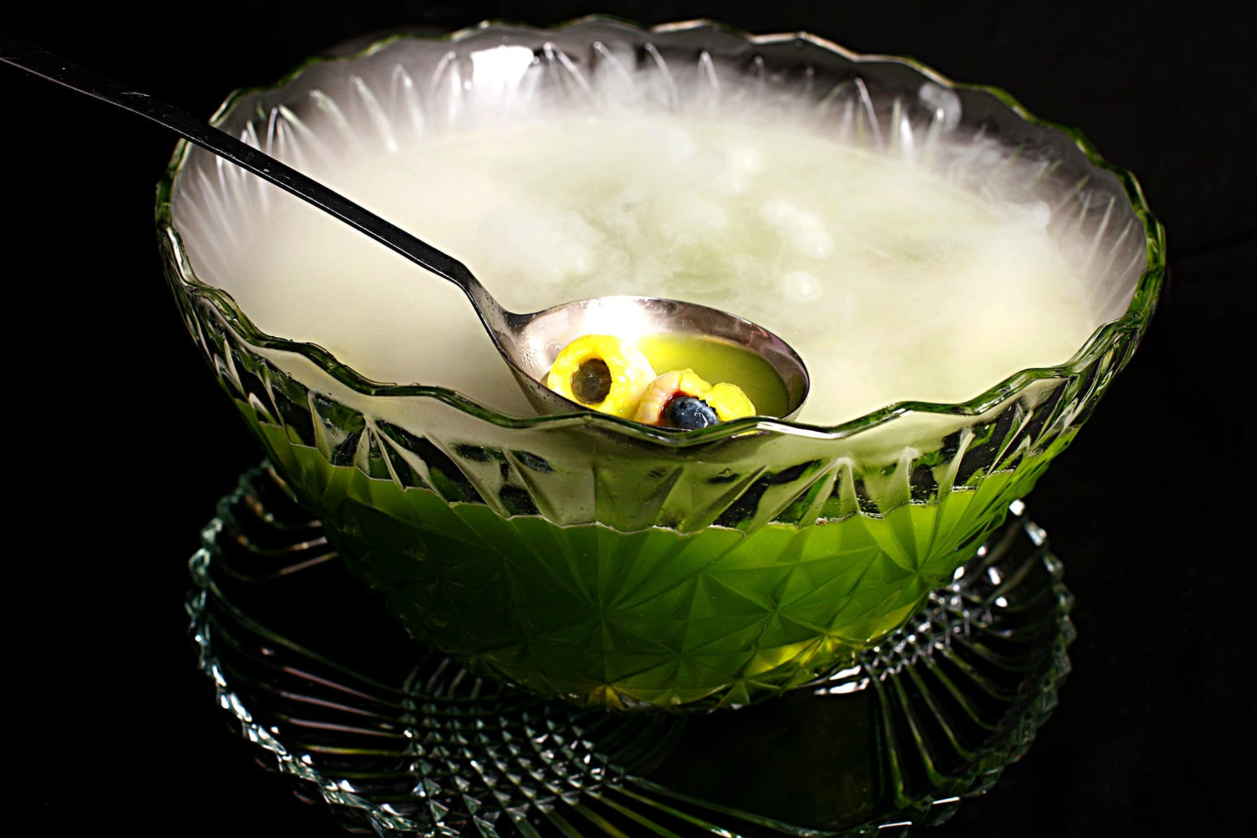 """A glass punch bowl with bright green halloween punch, and lychee """"eyeballs"""" floating in it. Vapour is rising from the punch bowl, from the dry ice used in it."""