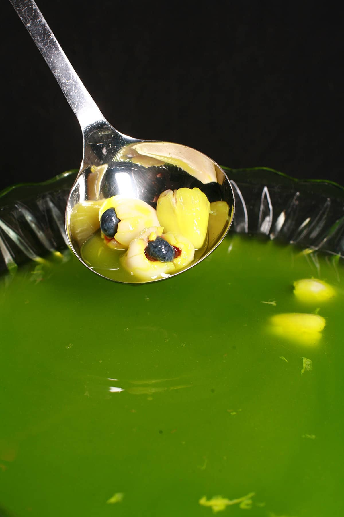 """A glass punch bowl with bright green halloween punch, and lychee """"eyeballs"""" floating in it."""