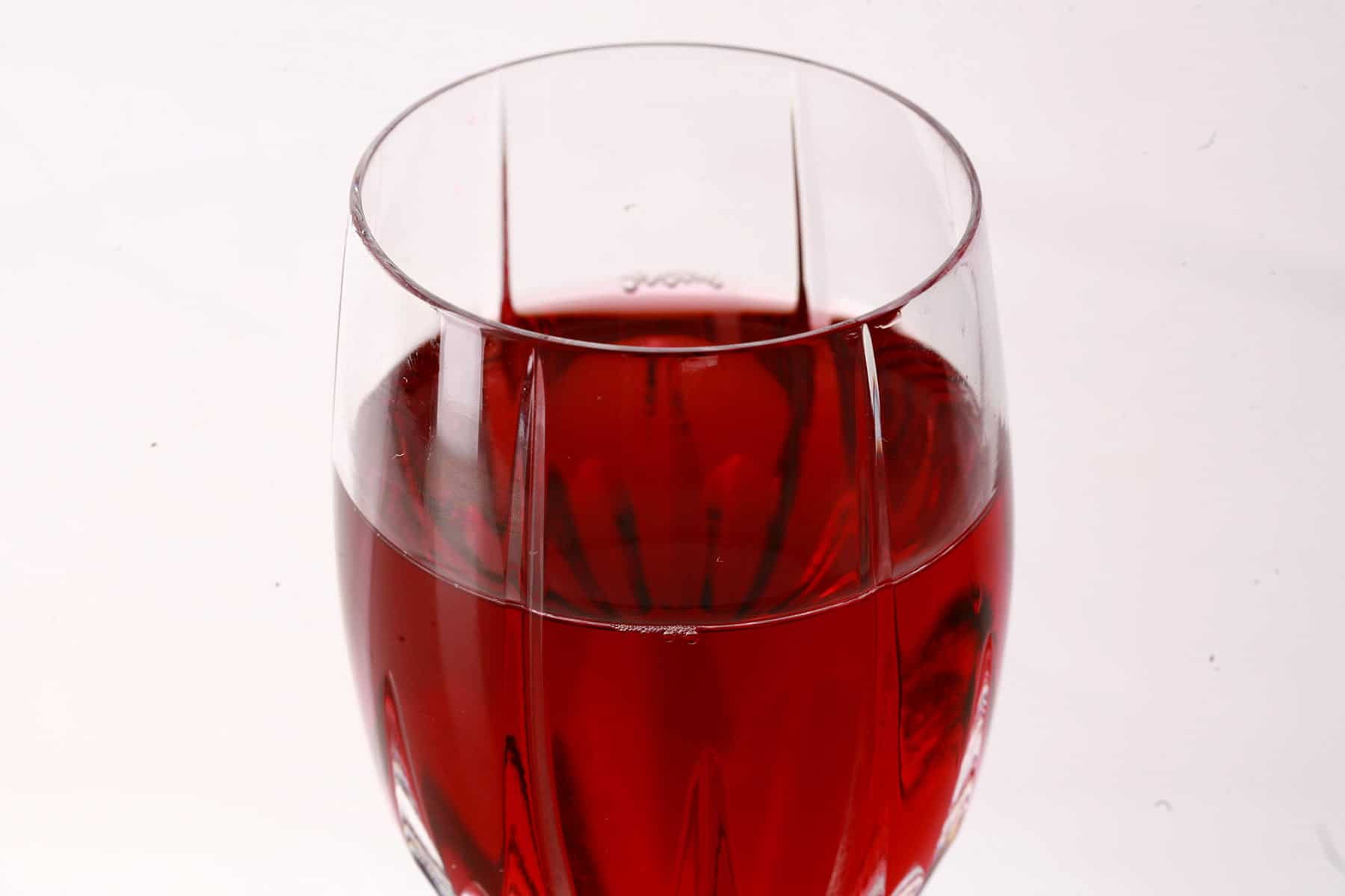 A faceted wine glass full of blueberry mead.