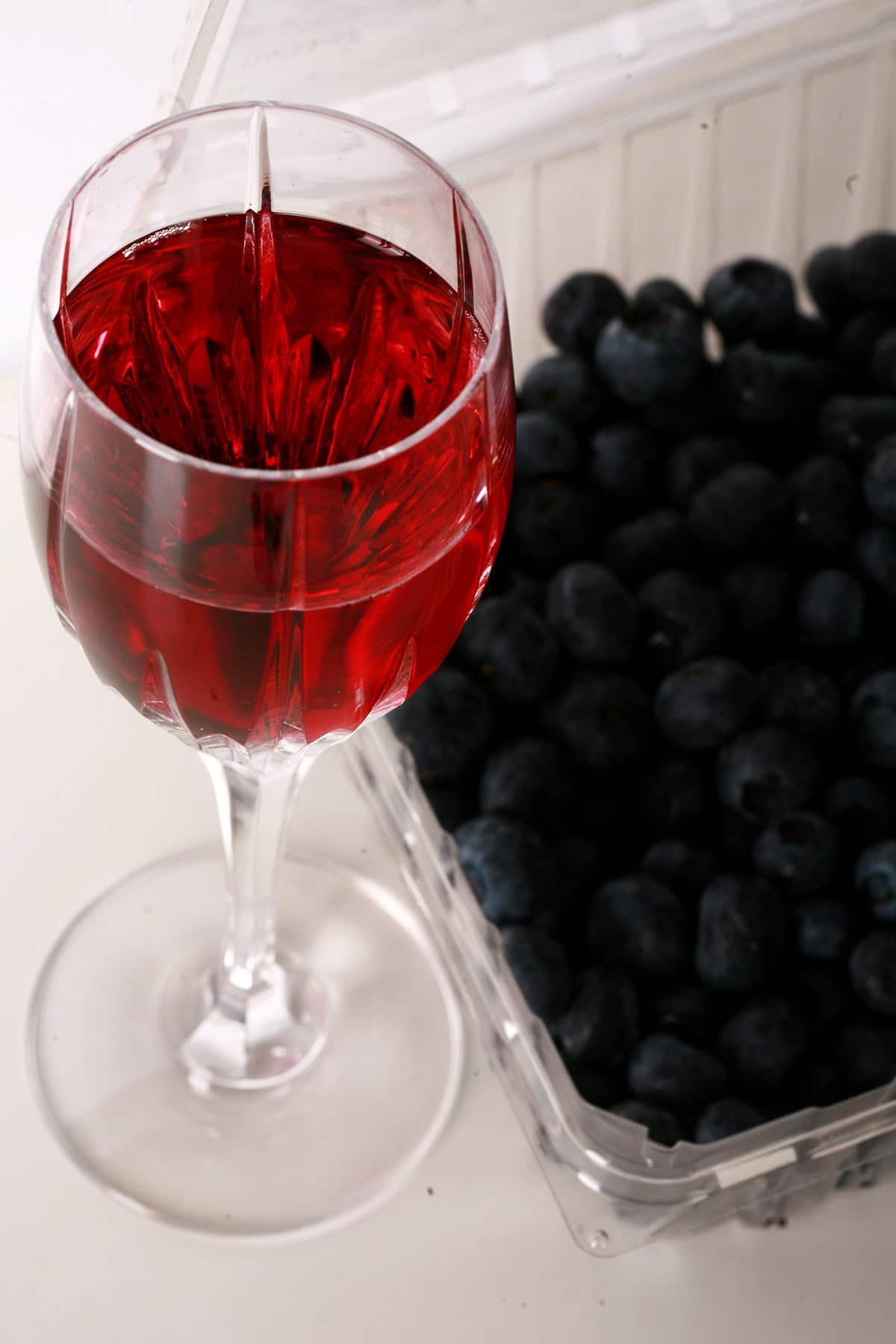 A faceted wine glass full of blueberry mead, with fresh blueberries beside the glass.