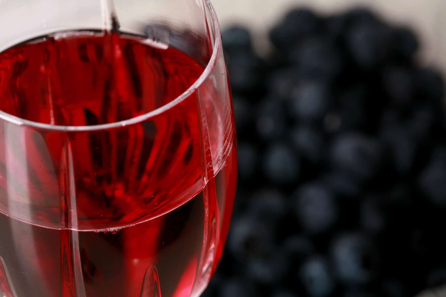 A faceted wine glass full of blueberry mead, with fresh blueberries behind the glass.