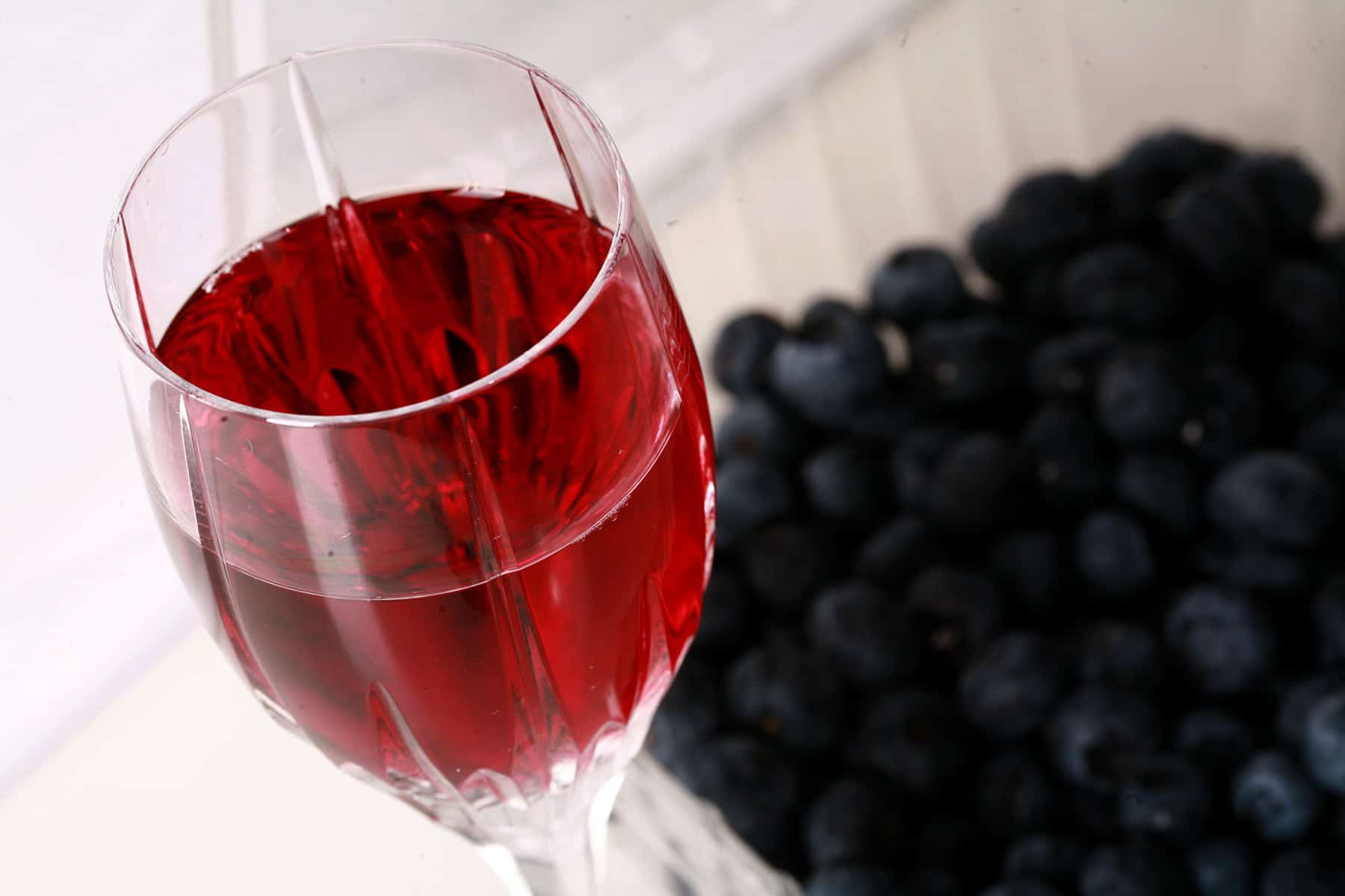 A faceted wine glass full of blueberry mead, with fresh blueberries at the base of the glass.
