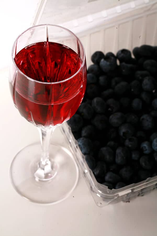 Close up photo of a glass of clear, light purple wine, with blueberries in the background