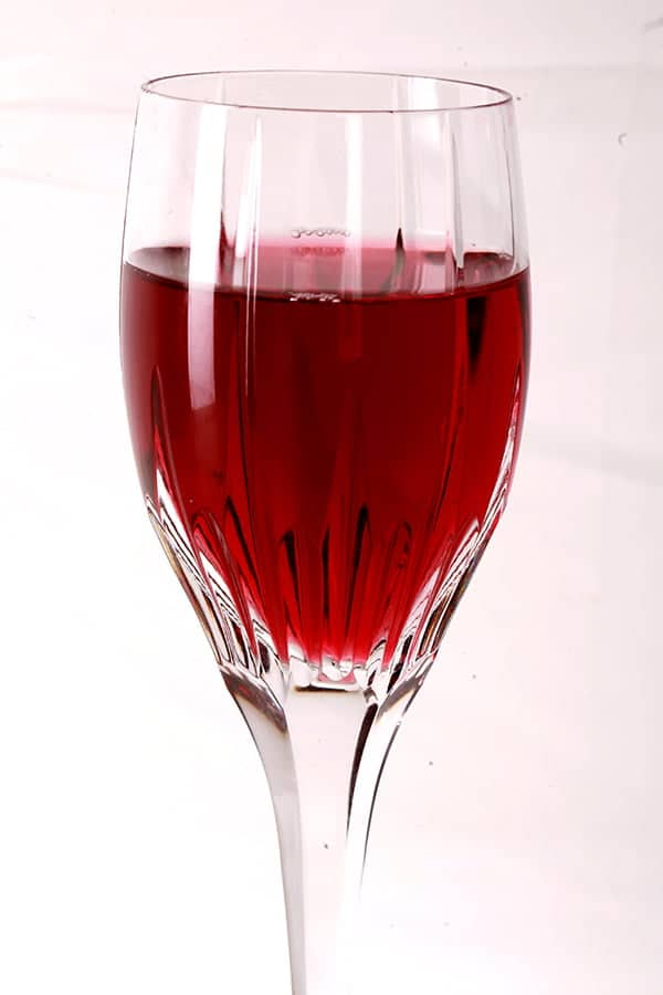 Close up photo of a glass of clear, light purple wine