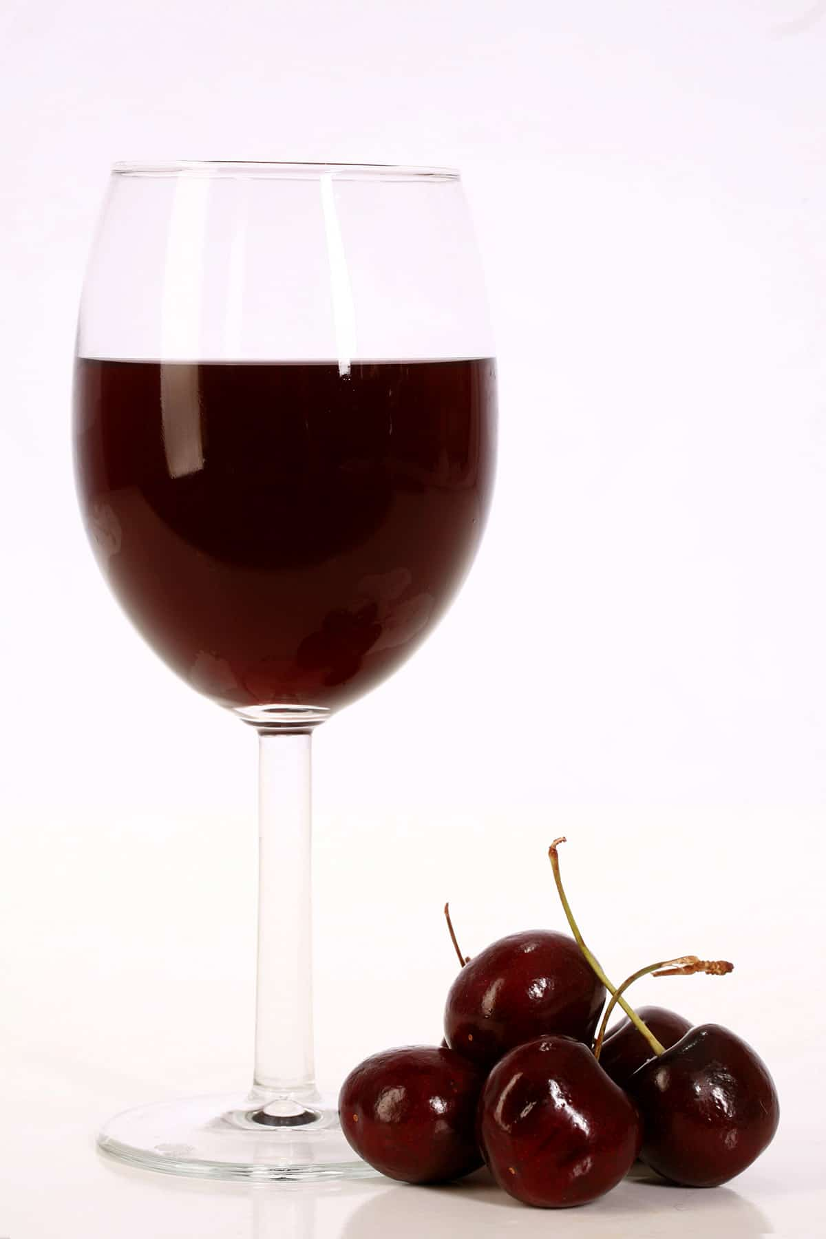A glass of dark red cherry wine, with several cherries at the base of it.