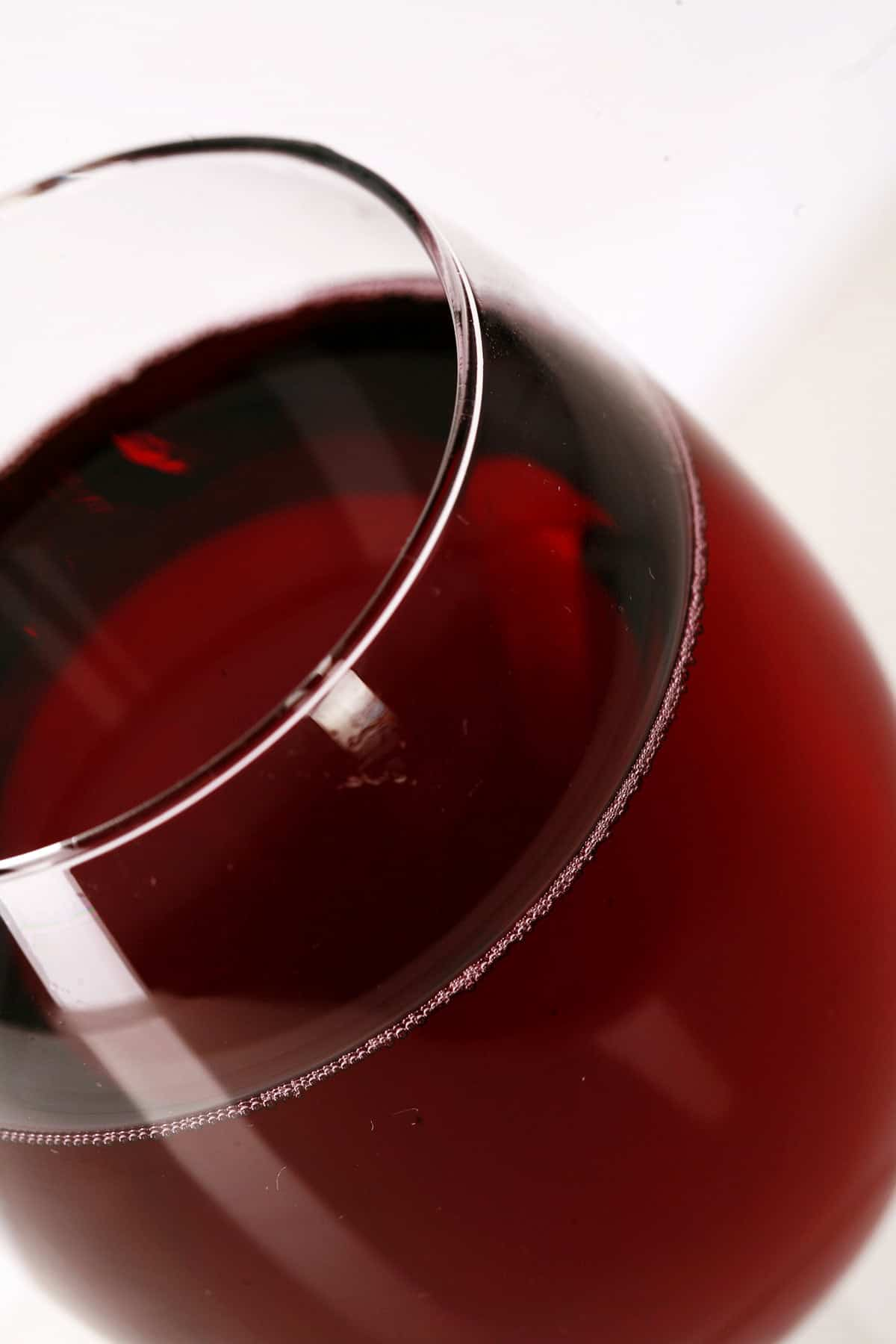 Close up view of a glass of homemade cherry wine.