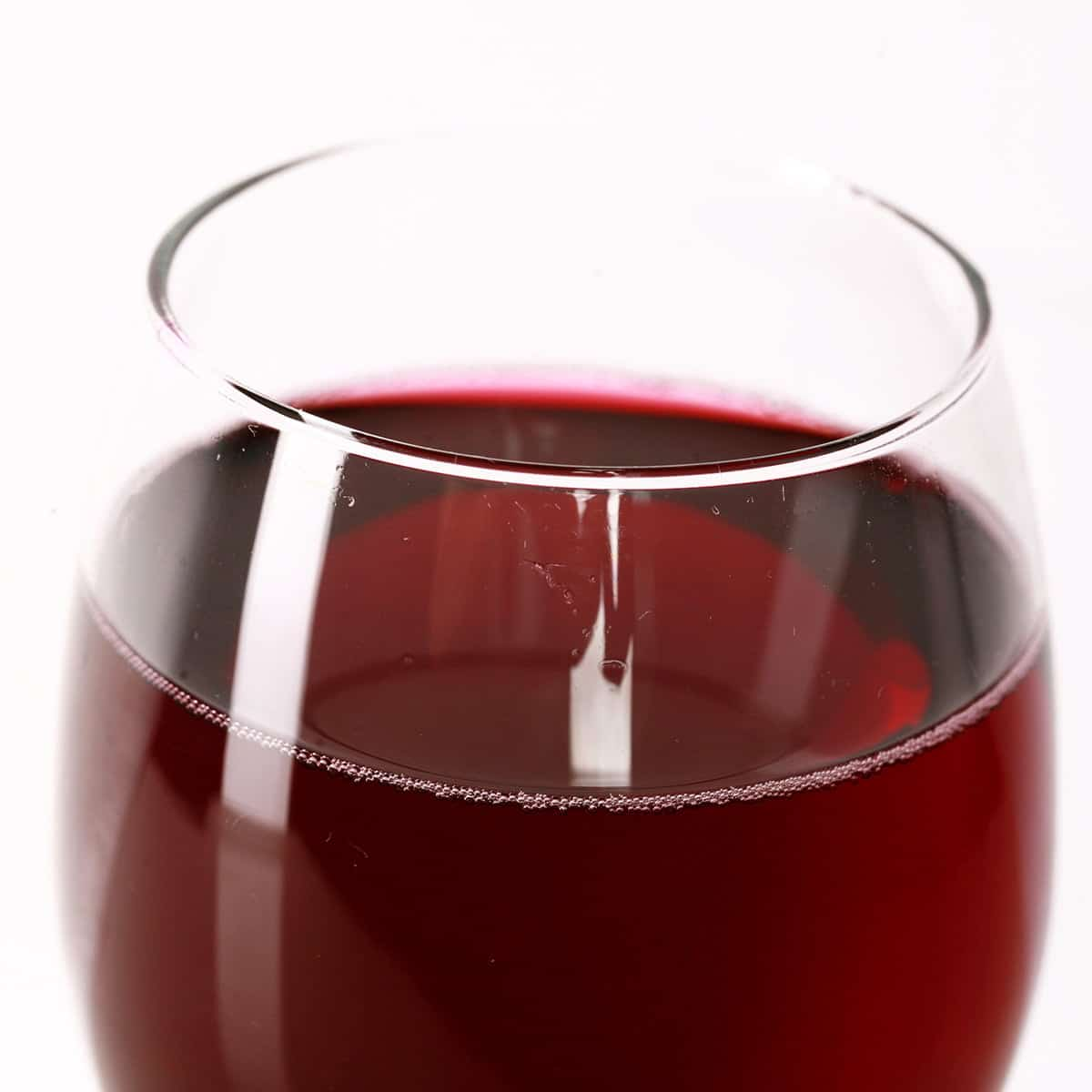 Close up view of a glass of red wine, made from this cherry wine recipe.