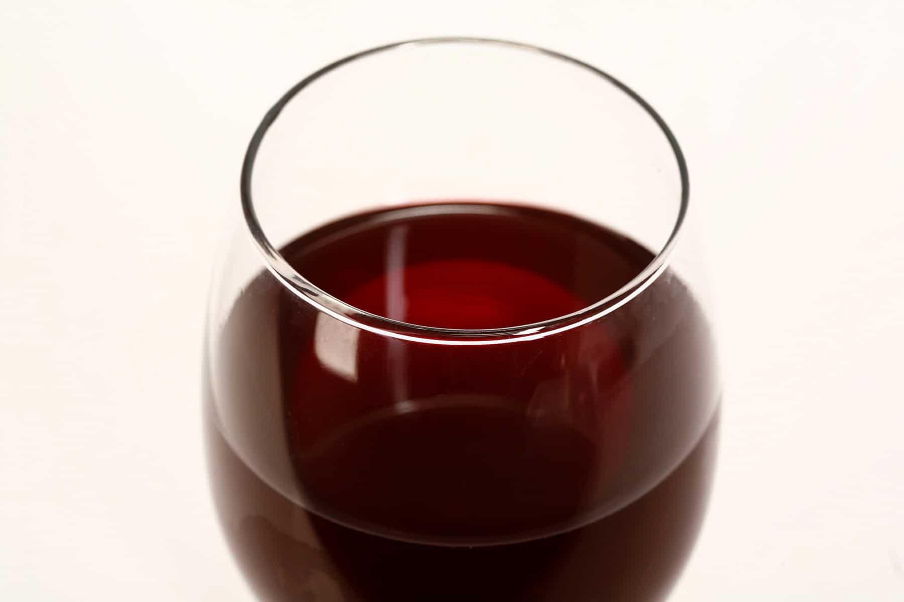 A glass of dark red cherry wine.