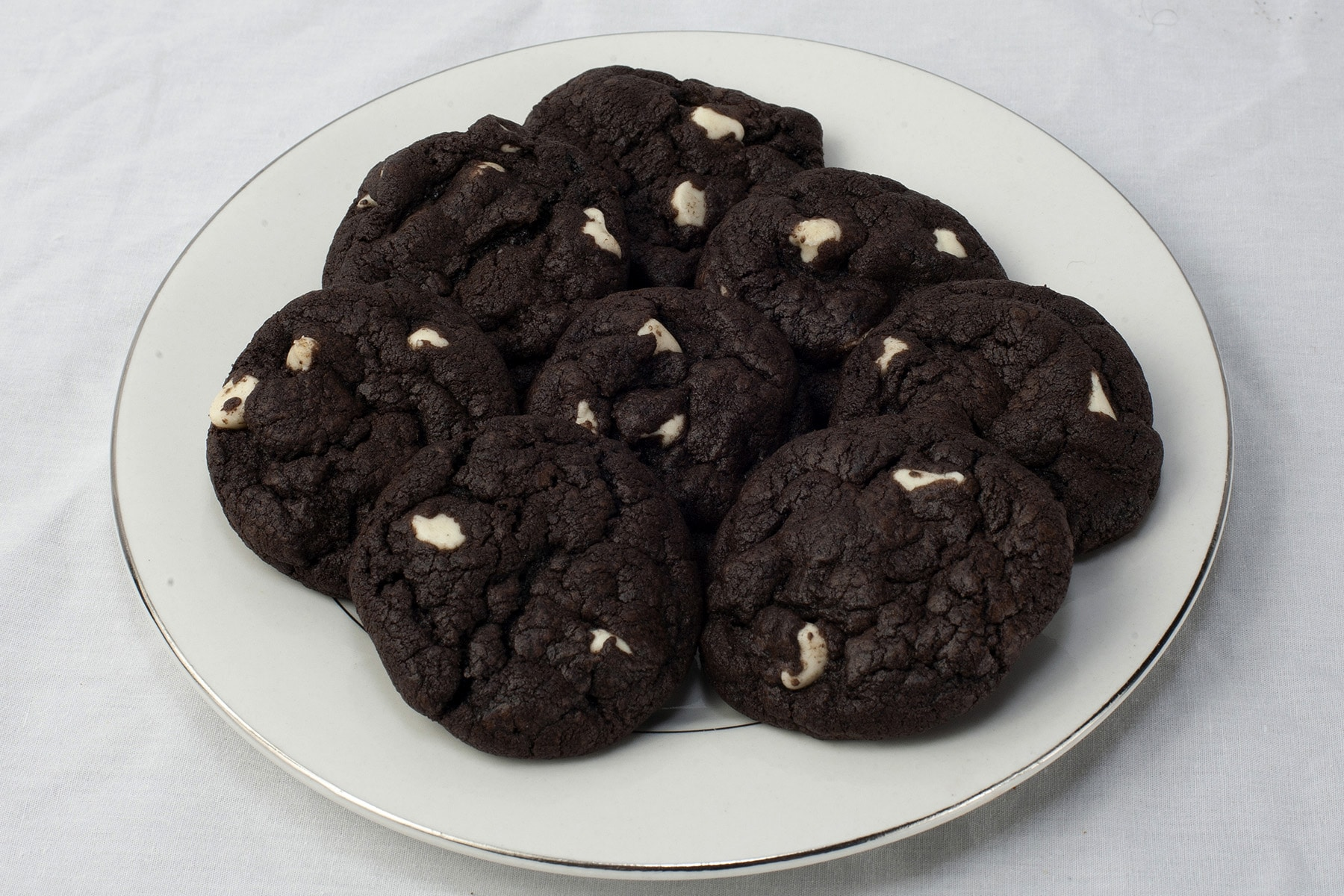 A plate of dark chocolate cookies with white chocolate chips.