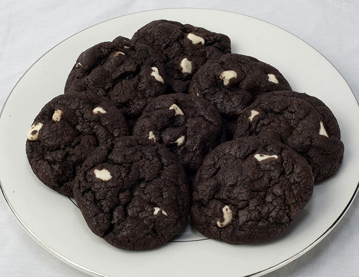 Plate of chocolate cookies with white chocolate chips.