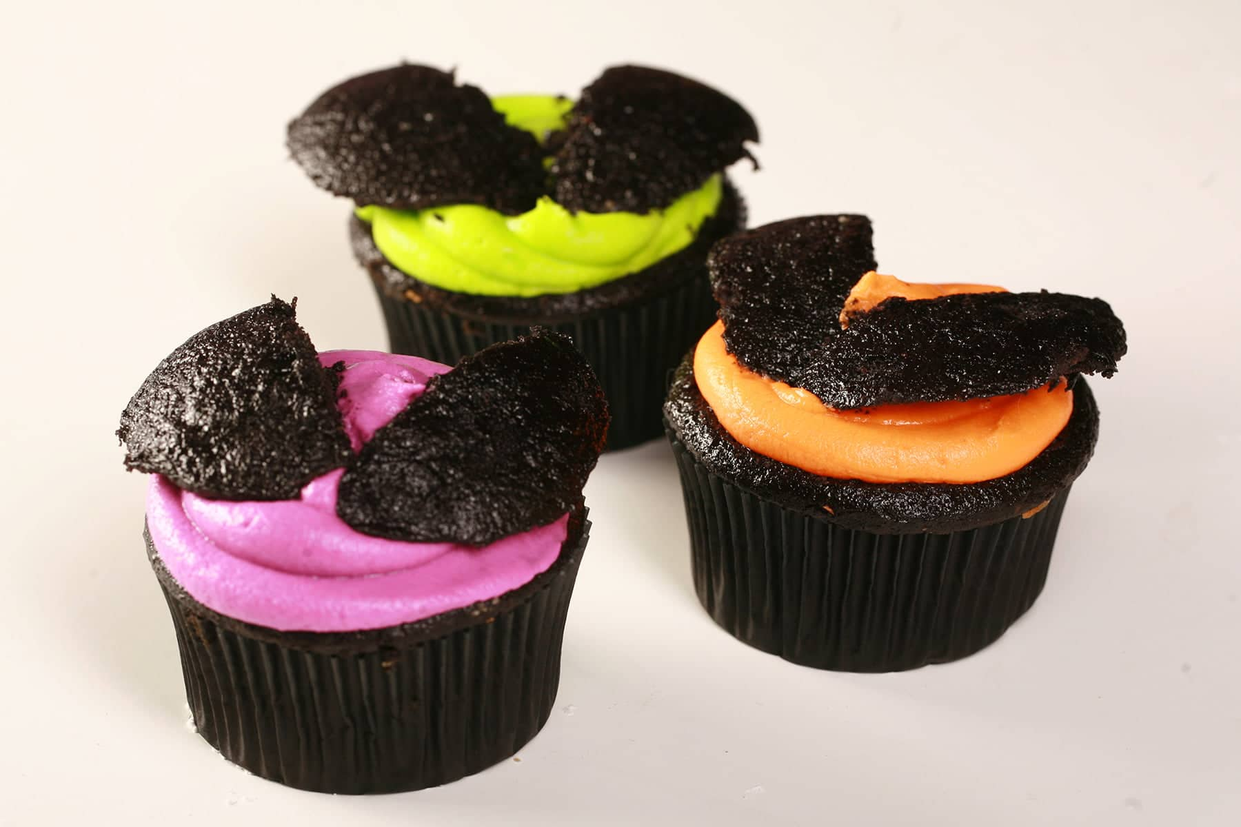 3 Easy halloween Bat Cupcakes - Black Velvet Cupcakes with the dome cut off, frosted with brightly coloured icing - electric purple, lime green, and orange - then the halved dome of the cupcake is re-positioned on top to form bat wings.