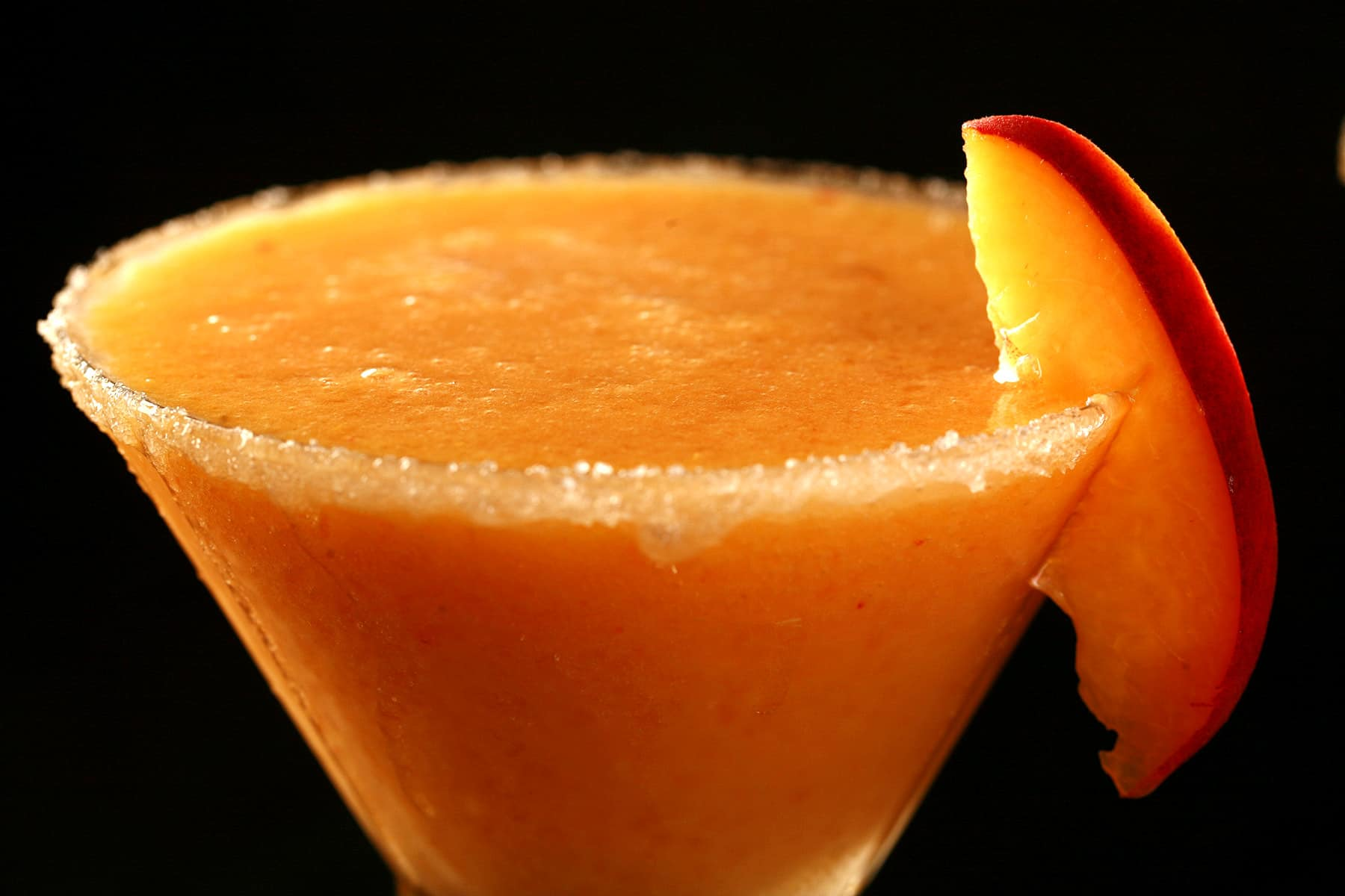 A close up view of a daiquiri made from fresh peaches. It's in a martini cocktail glass rimmed with sugar and garnished with a slice of peach.
