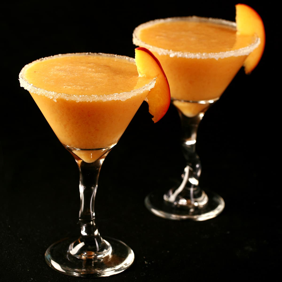 Two Fresh Peach Daiquiris in martini cocktail glasses. The glasses are rimmed with sugar and garnished with a peach slice.
