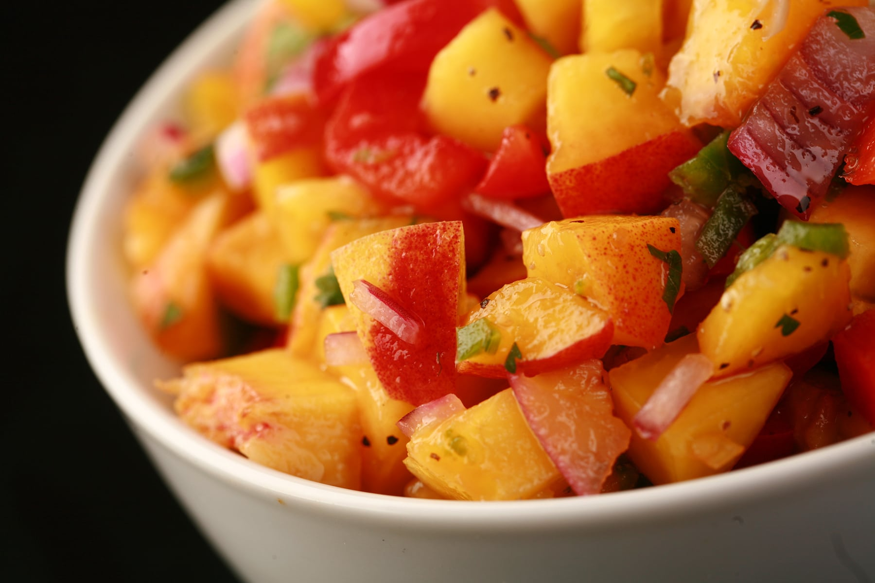 A close up photo of fresh peach salsa, with peaches, red pepper, red onions, jamapeno, and cilatro visible.