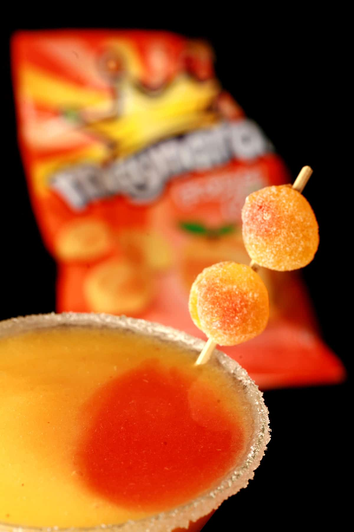 A close up view of a martini cocktail glass with fuzzy peach candy cocktail - a peach coloured slush with a round section of red slush in it, garnished with gummy candies. There is a bag of the namesake candy in the background.