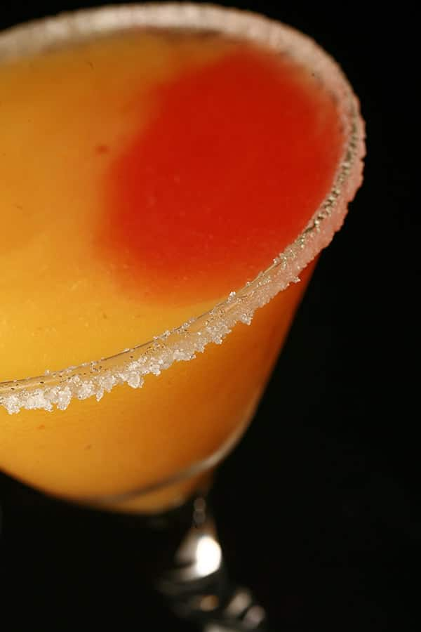 Close up image of a martini glass. It has a sugar rim, and orange and red coloured slush within.