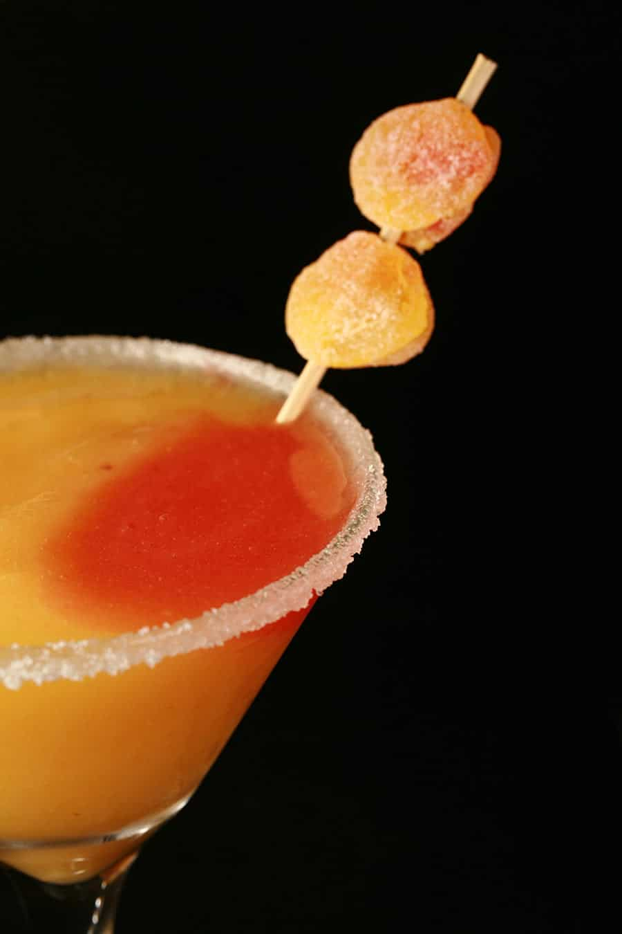 Close up image of a martini glass. It has a sugar rim, and orange and red coloured slush within. It is garnished with 2 peach shaped candies