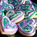 Close up view of a plate of heart shaped cookies decorated with swirls of teal and lavender over white.