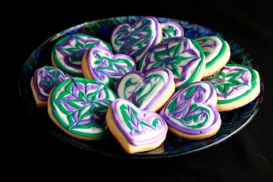 Plate of heart shaped cookies decorated with swirls of teal and lavender over white.