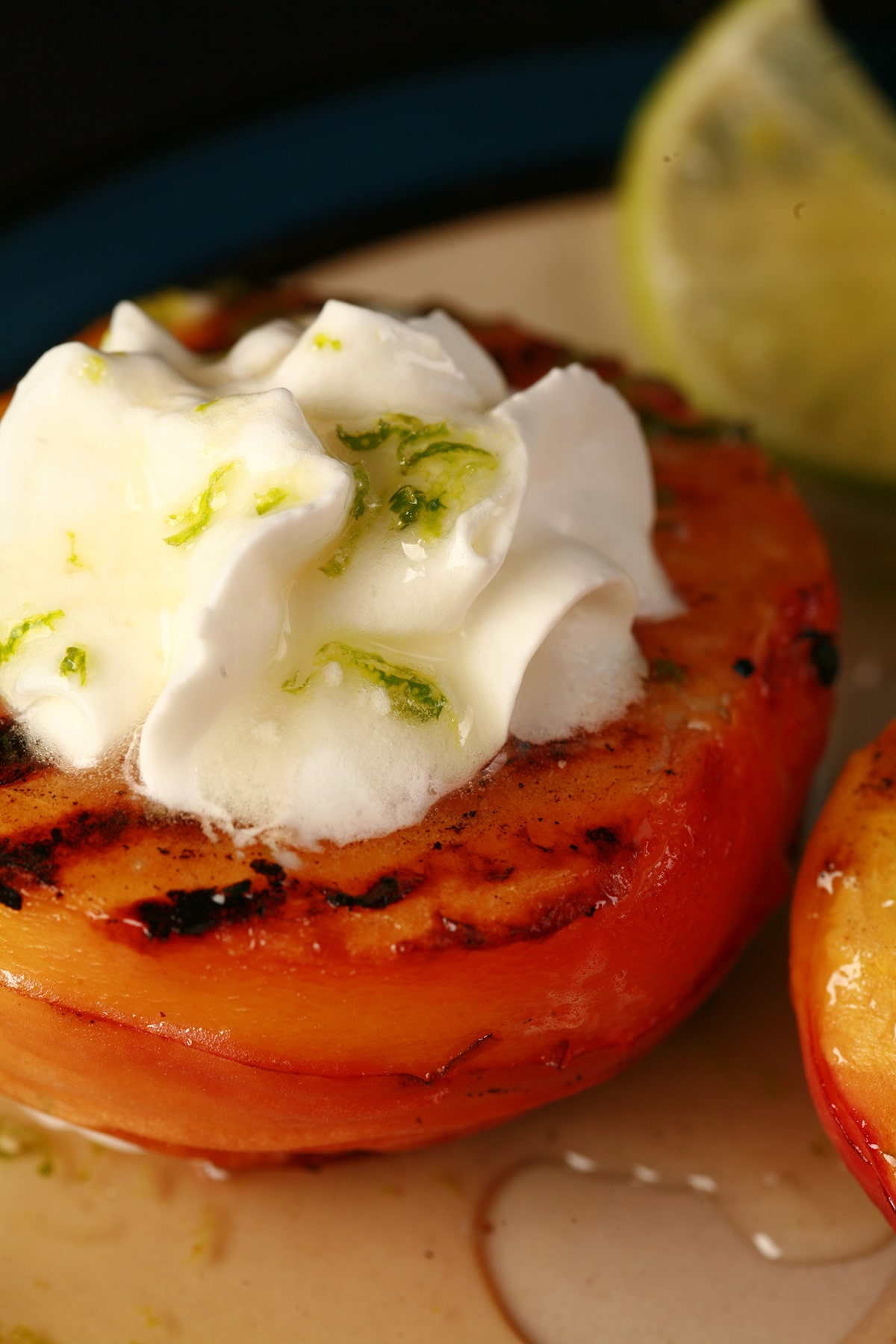 Two grilled peach halves on a plate, drizzled with lime honey. Each has a dollop of whipped cream on it.