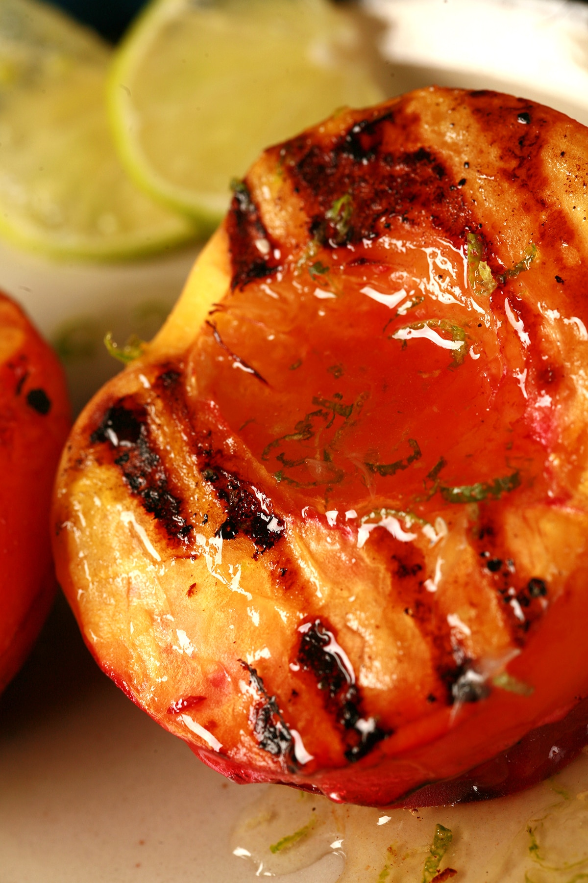 Two grilled peach halves on a plate, drizzled with lime honey.