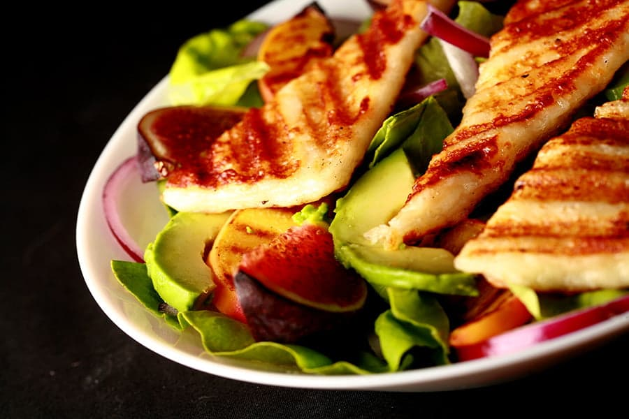 Image of a bowl of salad, with sliced figs, grilled peaches, and strips of grilled white cheese
