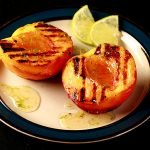 Image of two halves of a peach, with visible grill marks and honey drizzled over them