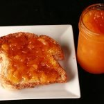 Close up photo of a small jar of orange coloured jam next to a piece of toast