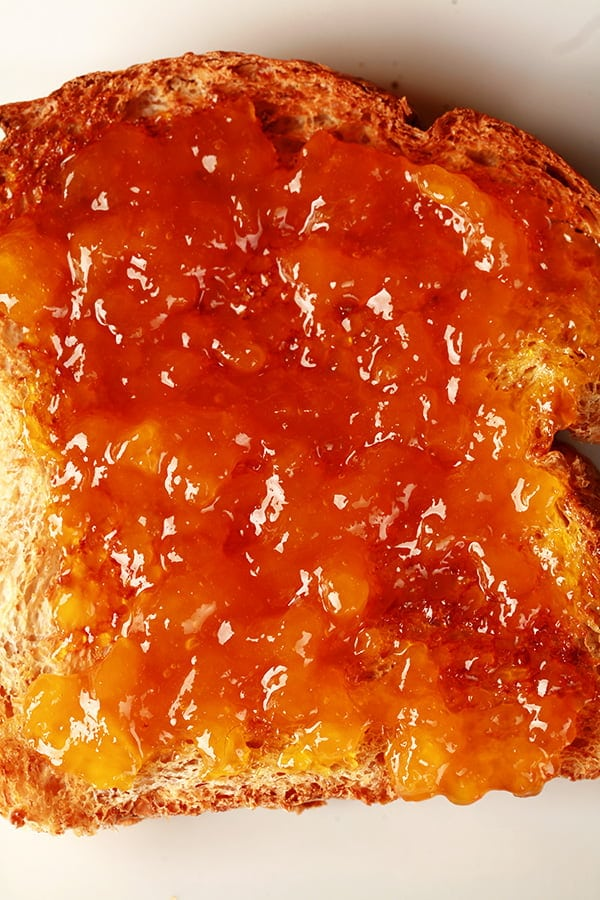 Close up photo of a piece of toast, spread with a smooth orange coloured jam