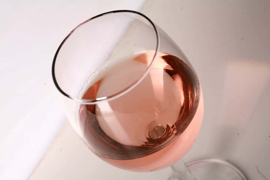 Close up photo of a single glass of pale pink wine