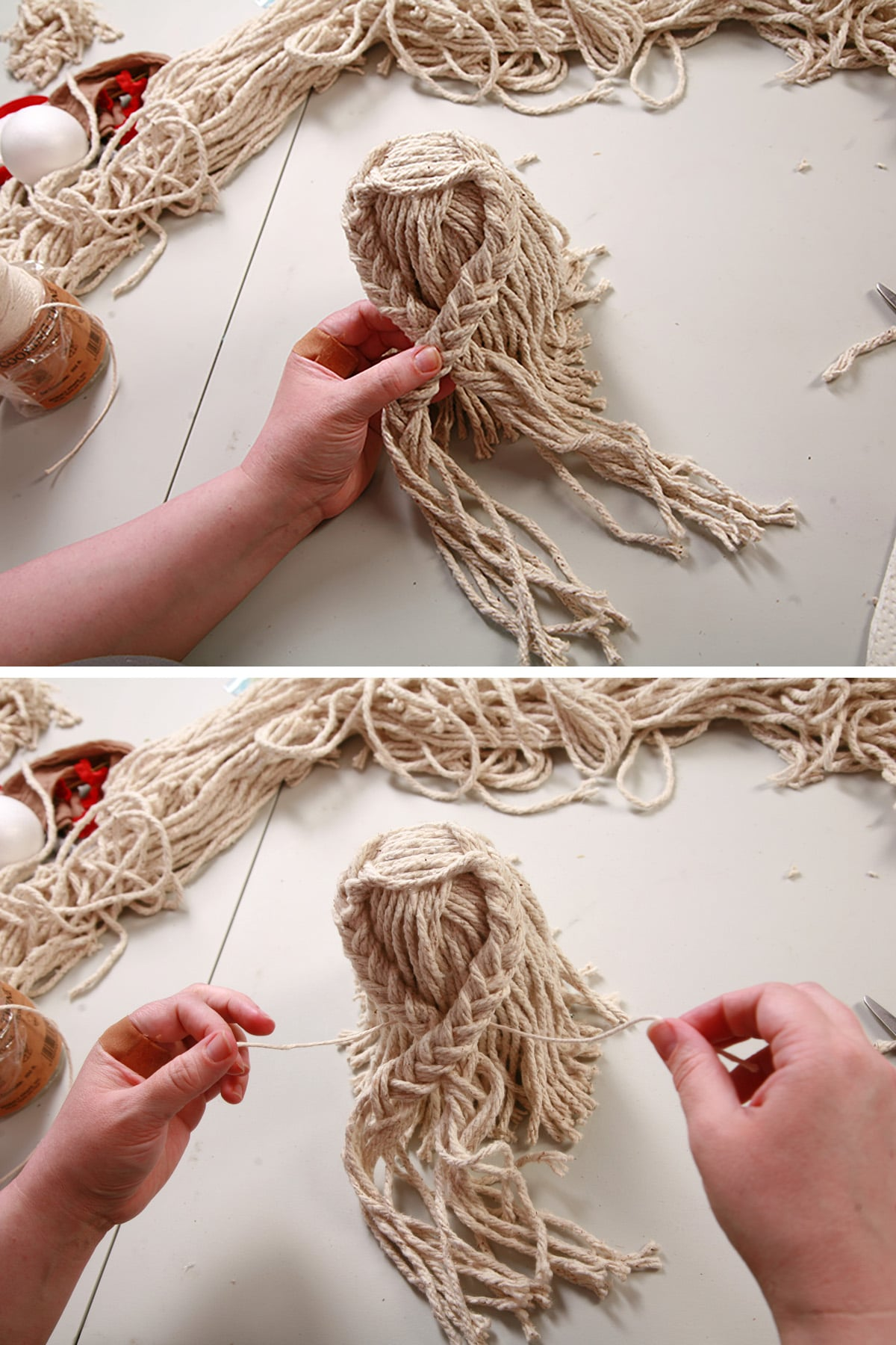 The two braids being pulled to the front of the mop doll and secured to make the arms.