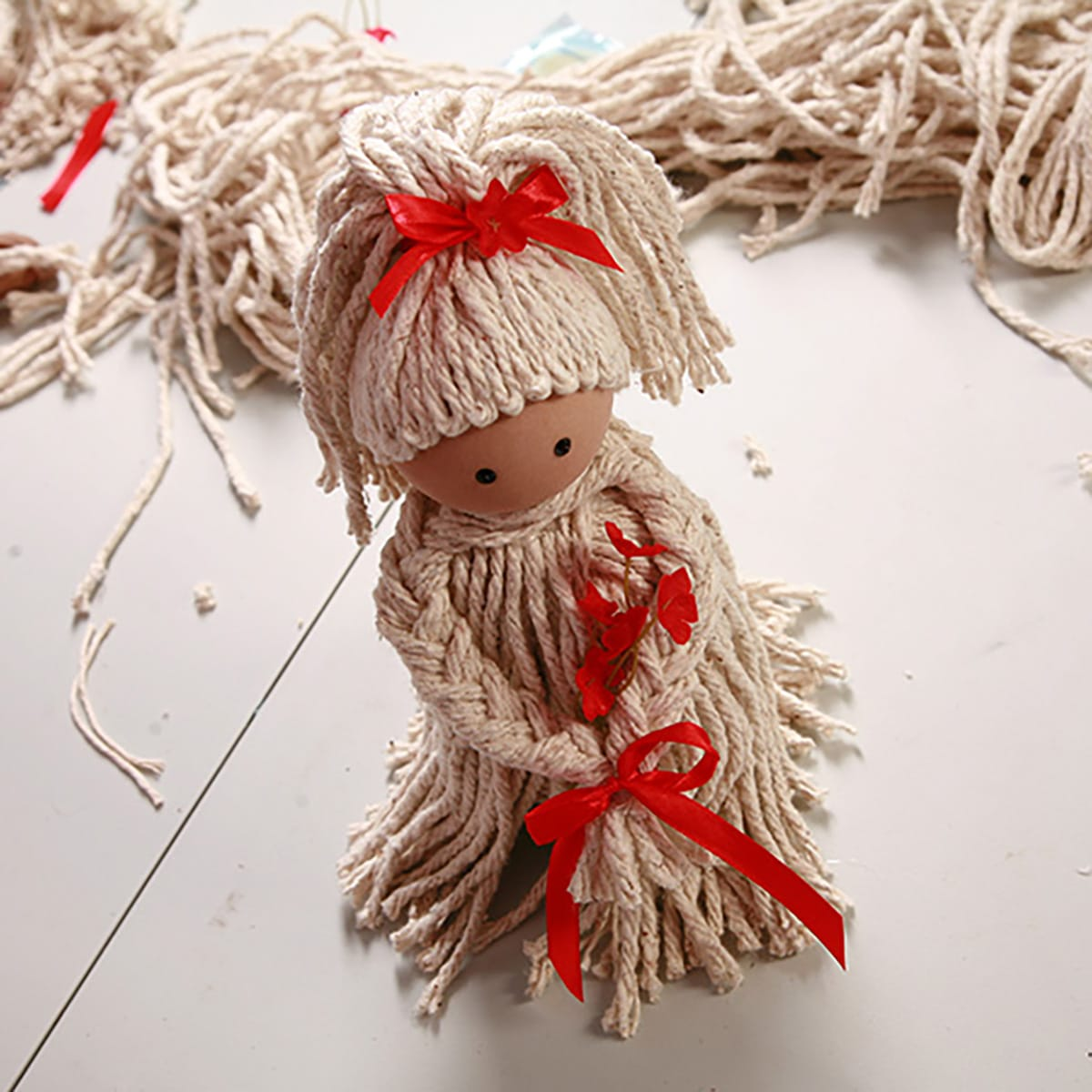 A finished mop doll air freshener on a work table.