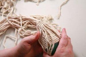 Placing folded lengths of yarn along the outer top edge of the mop doll's body