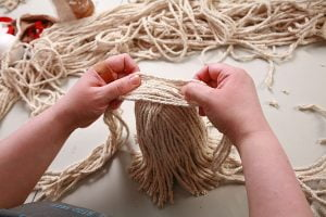 Placing 9 long strands of yarn over the hot glue patch on top of the mop doll's body