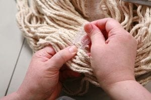 Carefully ripping out the seam that holds the mop yarns together