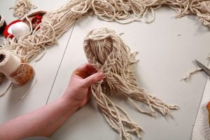 "Positioning the mop doll's braided ""arms"""