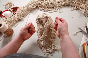 "Tying together the Mop doll's braided ""arms"""