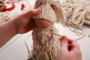 "Wrapping a piece of yarn around the ""neck"" of the mop doll"
