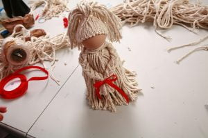"Mop doll with a red ribbon tied around the ""wrists"""