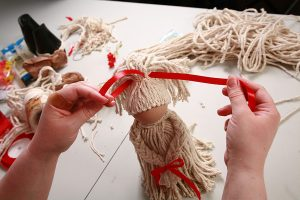Tying a ribbon around the mop doll's ponytail