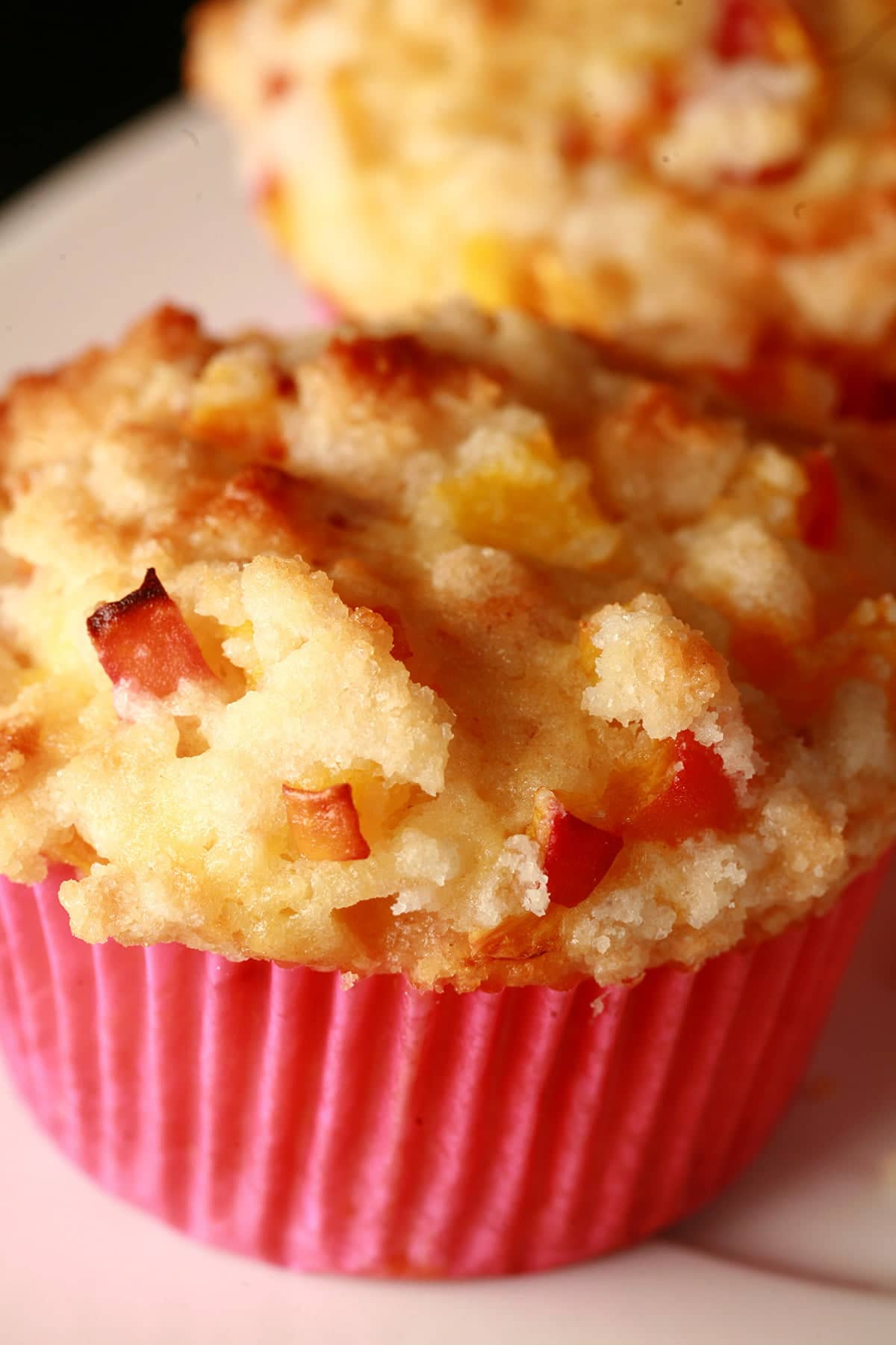 A close up photo of a Peach cobbler muffin.  The muffin has small pieces of peach and streusel on top, and is in a pink liner.