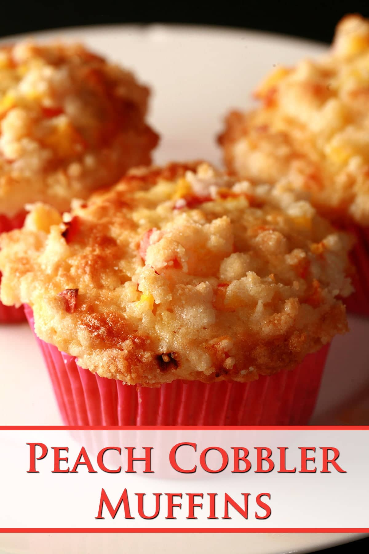 3 Peach cobbler muffins on a white plate. The muffins have small pieces of peach and streusel on top, and each has a pink liner.