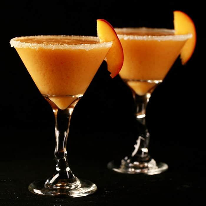 Photo of two martini glasses with peach coloured slush and a peach slice as a garnish