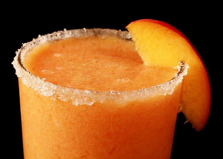 Close up photo of a martini glass with peach coloured slush and a peach slice as a garnish