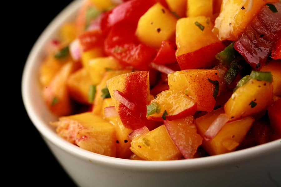 Close up photo of peach salsa, with chunks of peaches, red pepper, red onion visible.