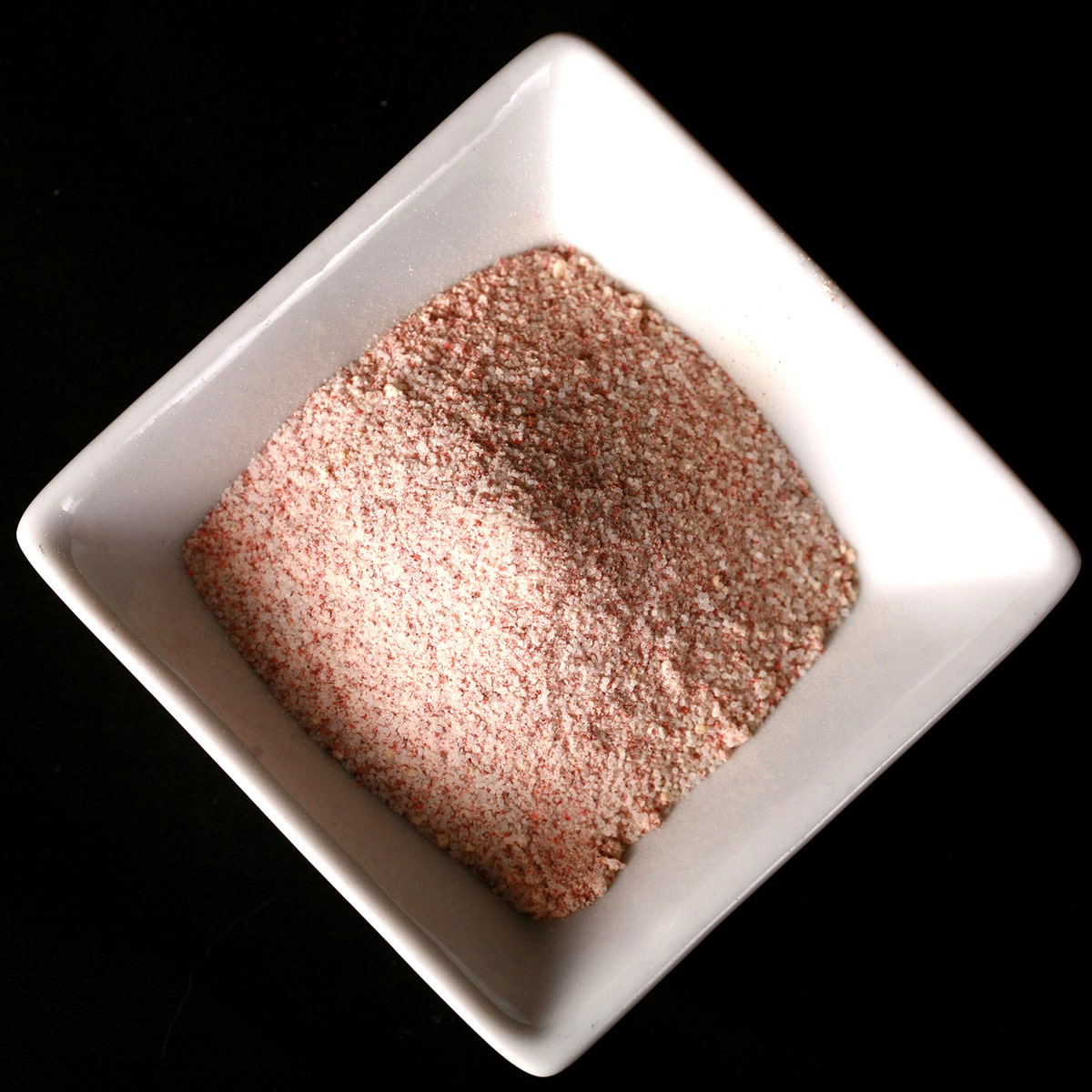 A small, square shaped white bowl with a pinkish seasoning salt mixture in it.